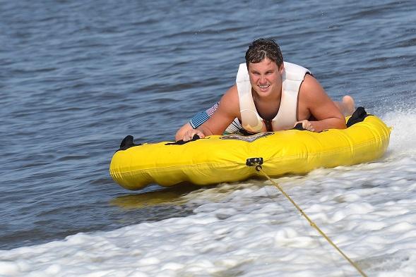 Teenager Tubing Outside Boat Wake